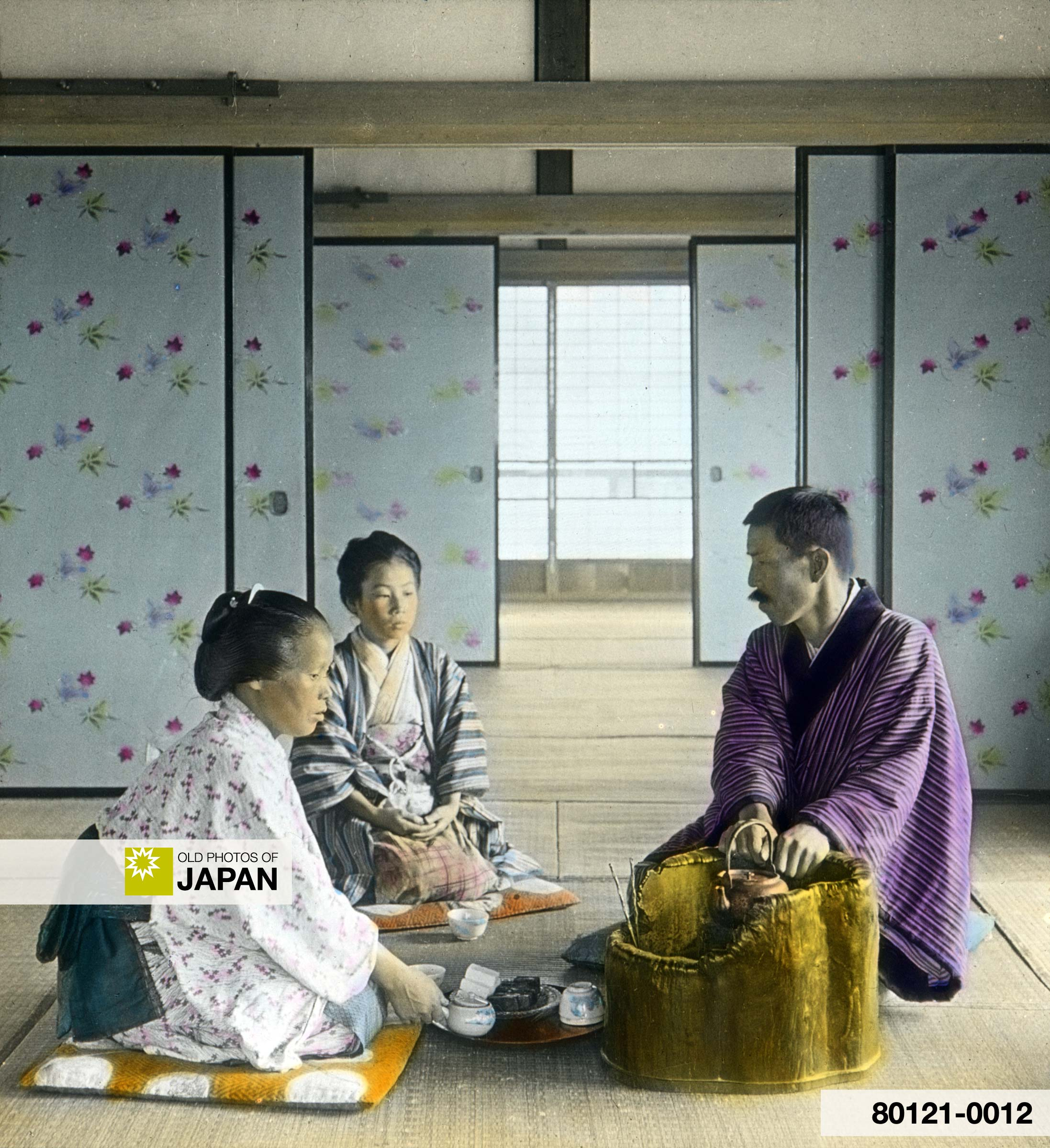 Japan. Man and Two Women Having Tea Inside Room.