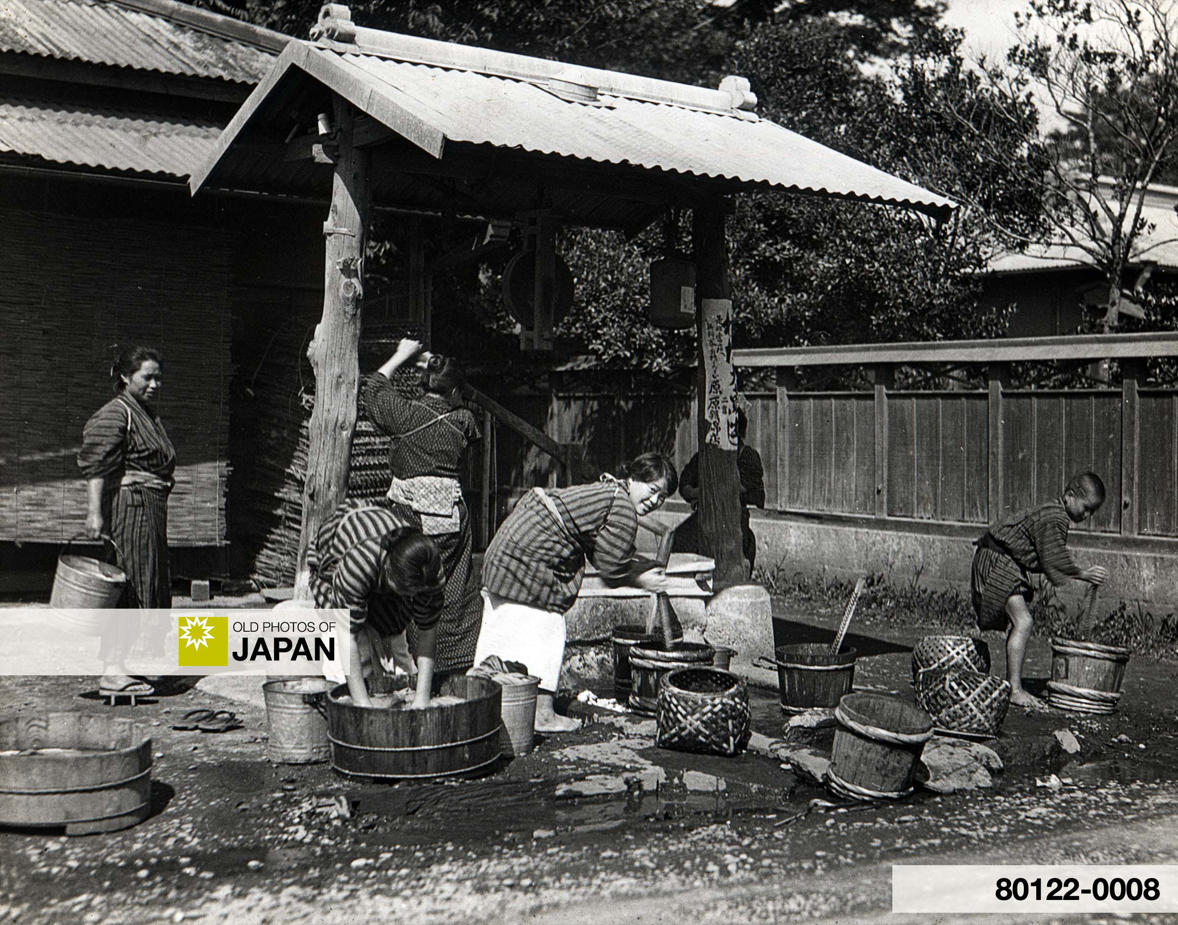 Women Washing Clothes in Small Tubs at Public Washing Place in Kamakura, Japan (1930).